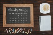 top view of arranged cup of coffee, empty notebook, colorful chalks and chalkboard with august calendar
