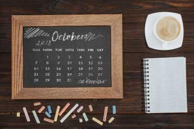 top view of arranged cup of coffee, empty notebook, colorful chalks and chalkboard with october calendar