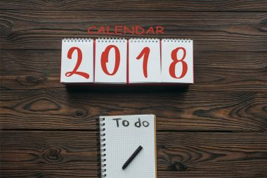 top view of 2018 calendar and notebook with to do lettering on wooden surface