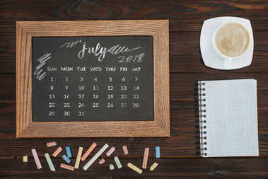 top view of arranged cup of coffee, empty notebook, colorful chalks and chalkboard with july calendar