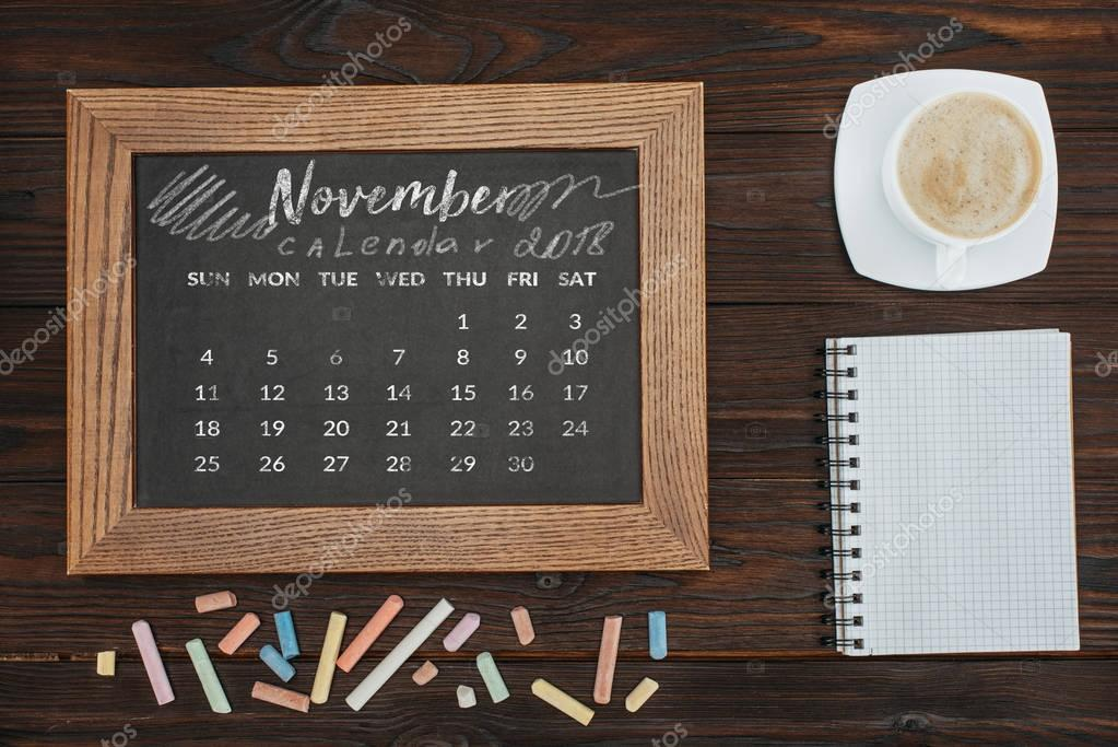 top view of arranged cup of coffee, empty notebook, colorful chalks and chalkboard with november calendar