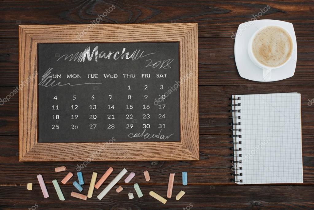 top view of arranged cup of coffee, empty notebook, colorful chalks and chalkboard with march calendar