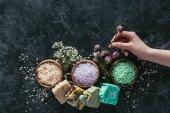 Fotografie oříznutý pohled ženské ruky s přírodní domácí mýdlo, sušené květiny a mořská sůl pro spa na černý mramor povrch