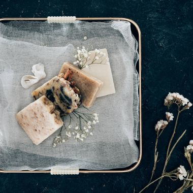 top view of natural homemade soap and dried flowers on gauze in tray