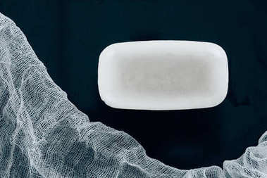 top view of white soap and gauze on black table