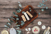 top view of homemade natural soap, eucalyptus and spa treatment on wooden board