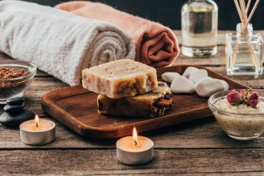 towels, homemade soap, spa treatment and candles on wooden tabletop