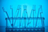 Fotografie skleněné trubice s kapalinou na stojan pro vědeckou analýzu na modré