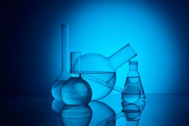 different glass flasks on reflecting table in laboratory on blue