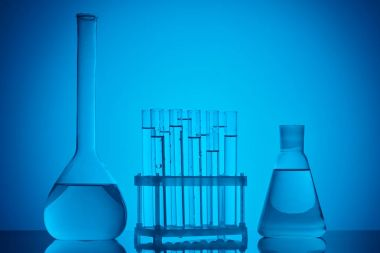 glass tubes on stand and glass flasks with liquid on table on blue
