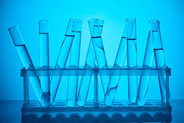 glass tubes with liquid on stand for scientific analysis on blue
