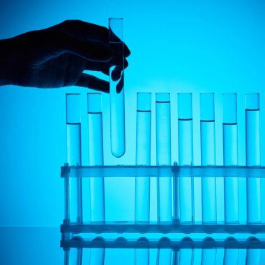 cropped image of female chemist taking glass tube with substance from stand on blue