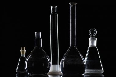 transparent glass flasks with substance in laboratory on black