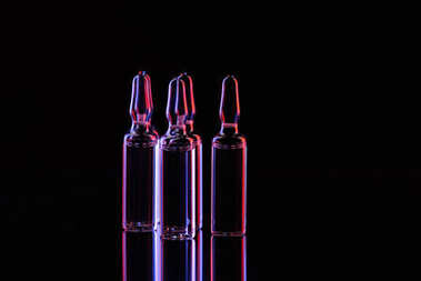 transparent glass ampoules with liquid on table on black