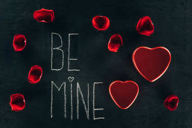 lettering BE MINE surrounded with rose petals and heart boxes on black surface, st valentines day concept