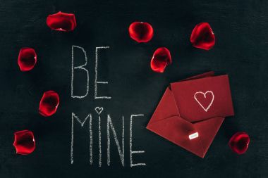 Lettering BE MINE surrounded with rose petals and red envelope on black surface stock vector