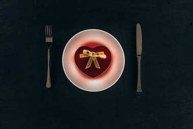 top view of present in shape of heart on plate with cutlery isolated on black, st valentines day concept