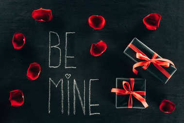 Lettering BE MINE surrounded with rose petals and gift boxes on black surface stock vector