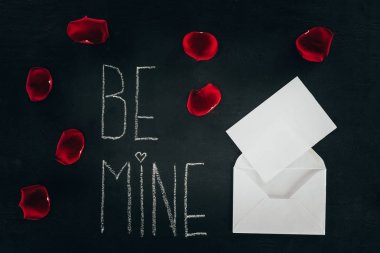 Lettering BE MINE surrounded with rose petals and envelope on black surface, st valentines day concept stock vector