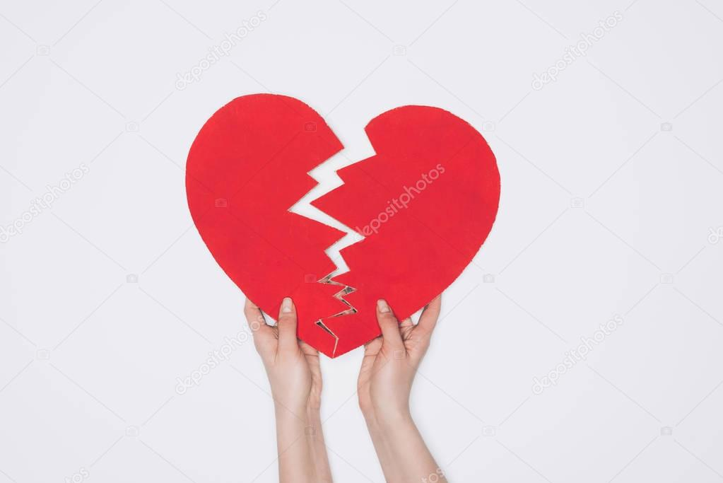 cropped shot of braking red heart isolated on white