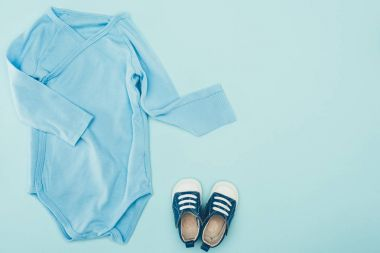 top view of baby bodysuit and shoes isolated on blue