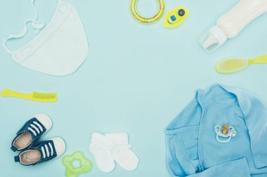 top view of baby clothes and equipment isolated on blue