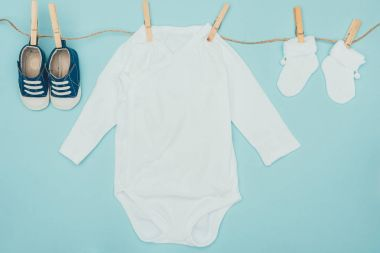 top view of baby clothes drying on rope isolated on blue