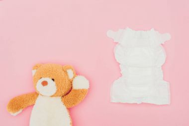 top view of teddy bear and unused diaper isolated on pink