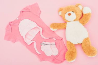 top view of teddy bear with baby clothes isolated on pink
