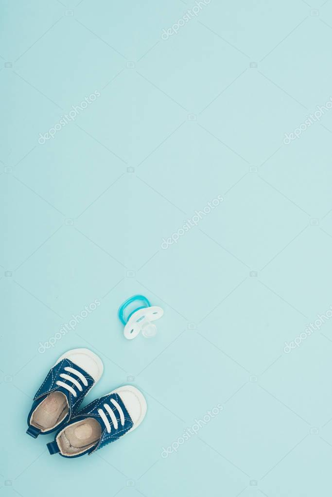 top view of baby shoes and dummy isolated on blue