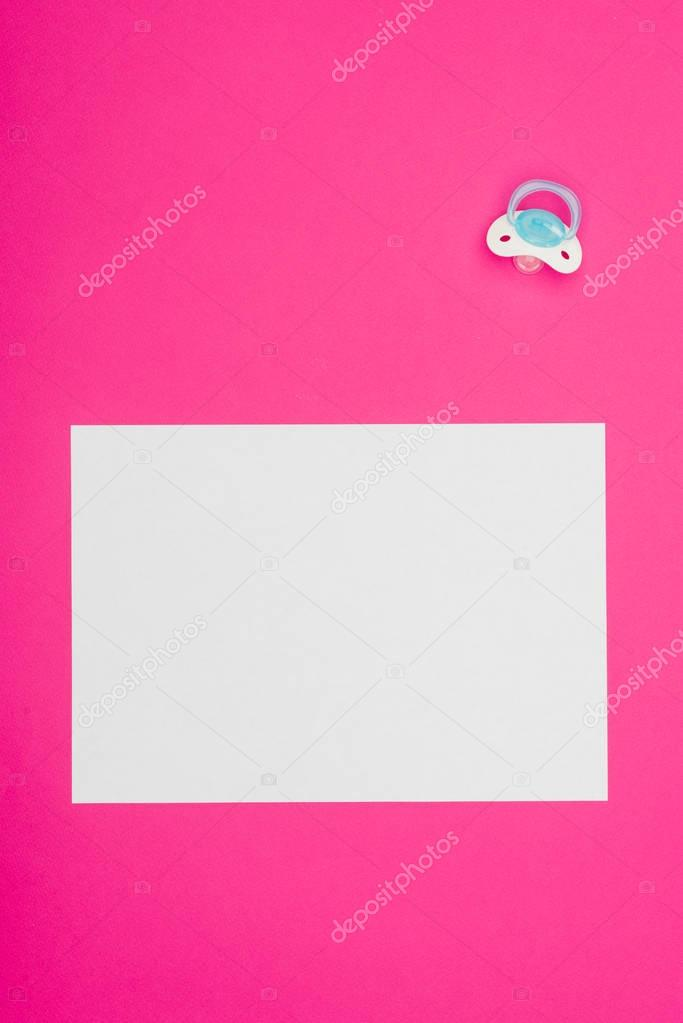 top view of empty board with baby dummy isolated on pink