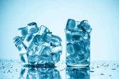 Eiswürfel in Glasnähe und im Glas schmelzen, auf weiß mit Tropfen