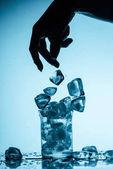 Fényképek részleges kilátás nyílik a személy jégkockát dobott üveg