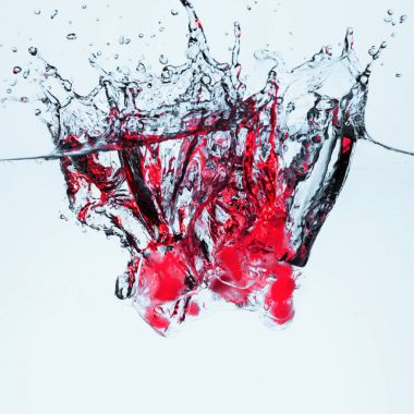 ice cubes with berries in water with splash, isolated on white