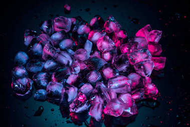 close up of pink melting ice cubes on black