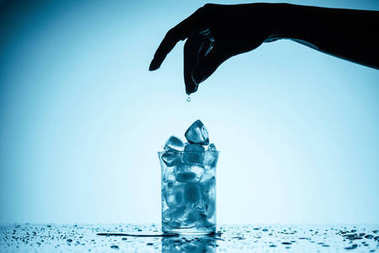 cropped view of person throwing ice cubes into glass