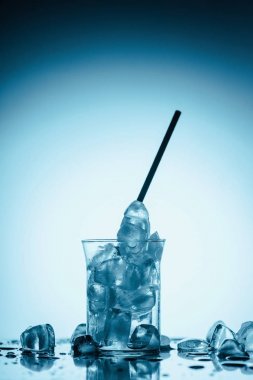 melting ice cubes in glass with straw, on white