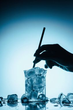 cropped view of person with straw and full glass on melting ice cubes