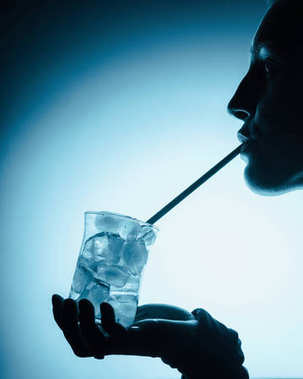 silhouette of woman drinking cold water with ice cubes with straw