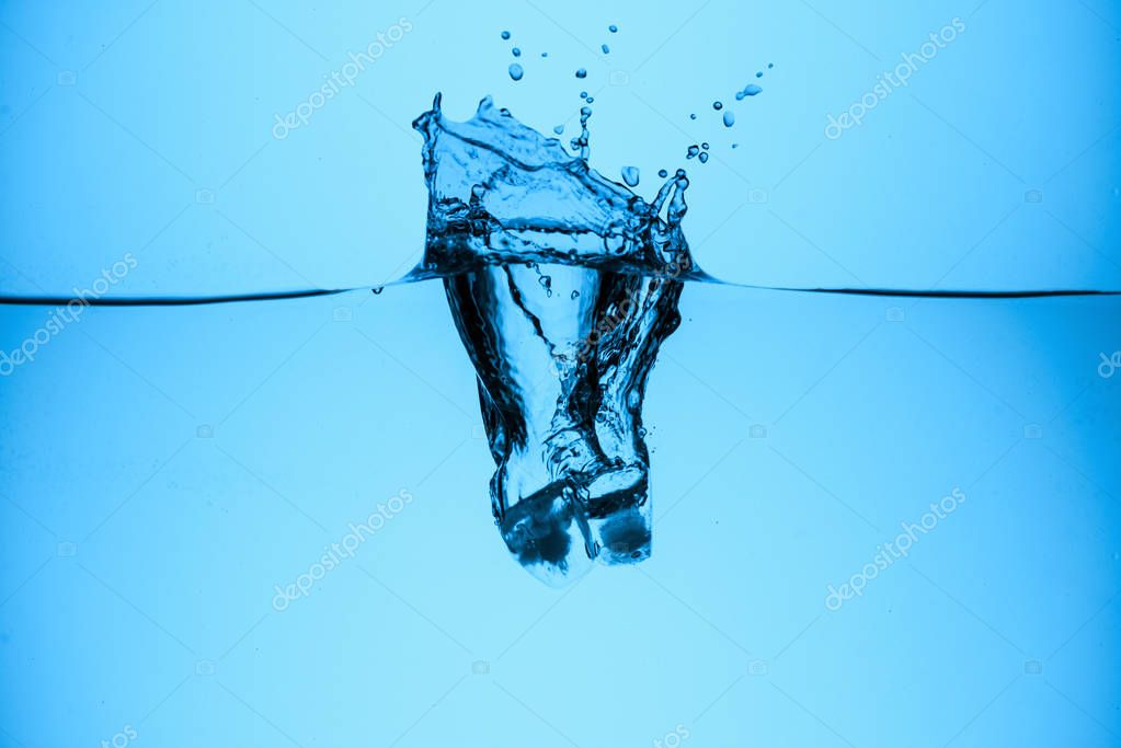 ice cube splashing in water, isolated on blue