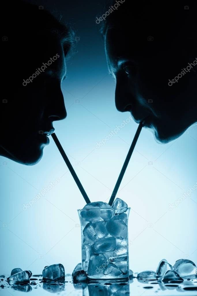 silhouettes of girls drinking cold water with ice cubes from one glass with straws