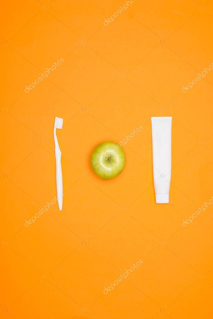 top view of toothbrush, apple and tube of toothpaste, isolated on orange