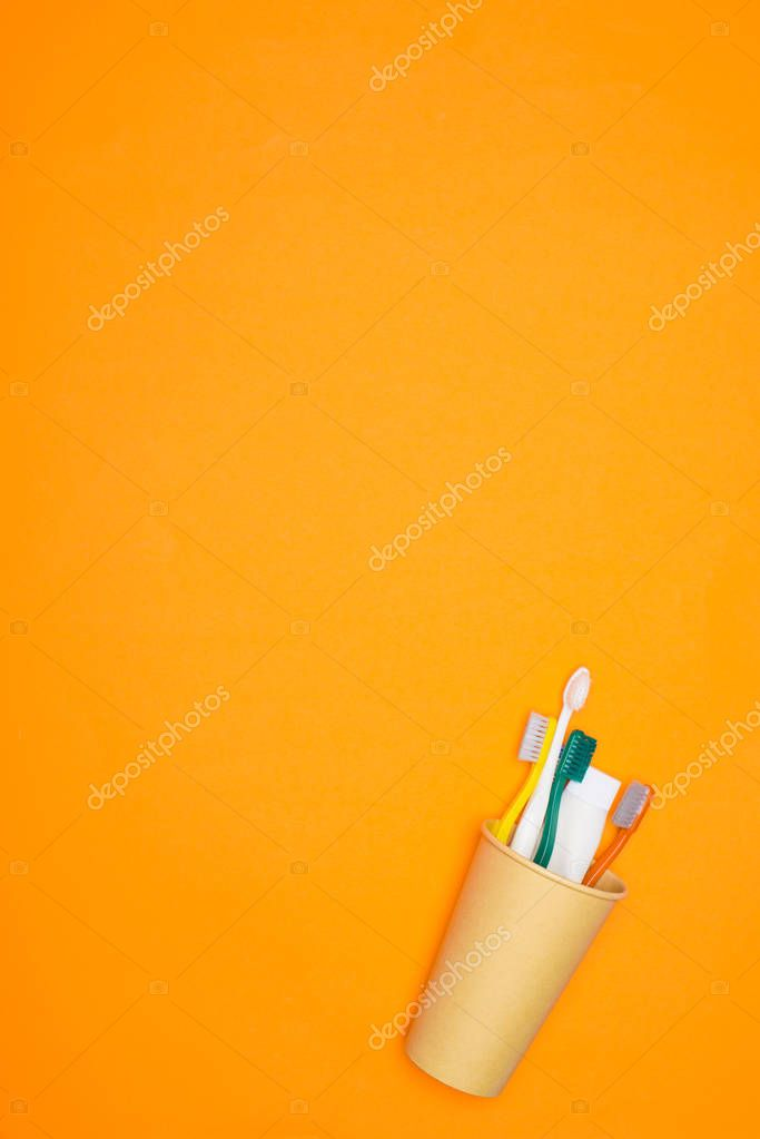 top view of toothbrushes and toothpaste in paper cup, isolated on orange