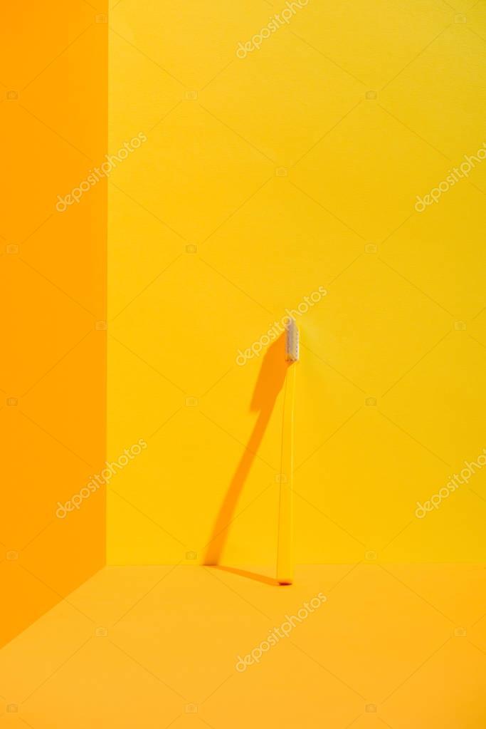 yellow toothbrush standing at orange wall
