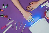 cropped image of woman holding hand near working uv lamp