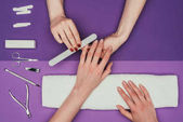 cropped image of nail technician filing nails to customer with nail file