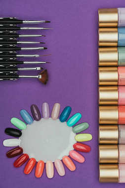 top view of nails polishes, brushes and palette isolated on purple