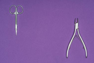 top view of scissors and nail nippers isolated on purple