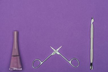 top view of nail polish and open scissors isolated on purple