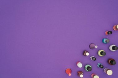 top view of colored nail polishes isolated on purple